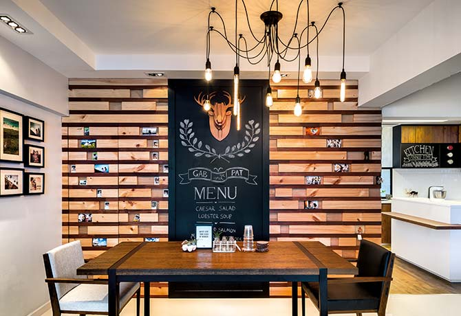 A wall made from strips of wood was hand-crafted, and a full-height chalkboard hides the entrance to a storeroom