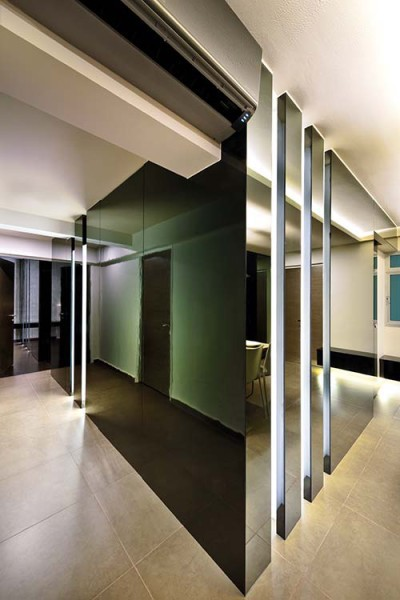 Tinted mirrors turn the corner into the passageway to the bedrooms – tight spaces like these  benefit from the shiny, reflective properties of  the mirror
