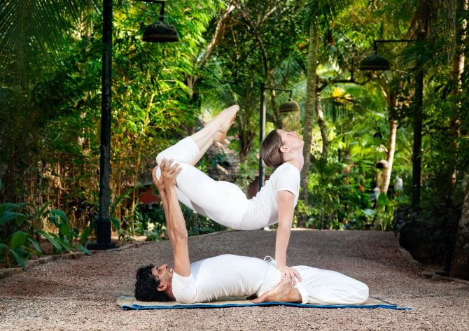 14290587 - man and woman doing acroyoga in white cloth in the garden
